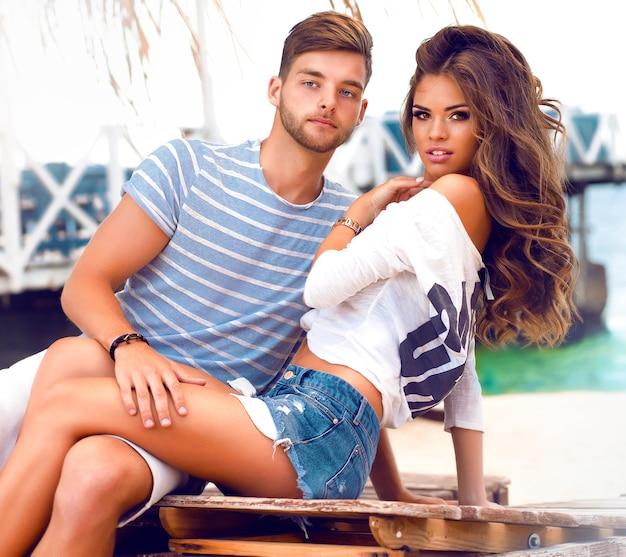 Retrato de moda ao ar livre de casal feliz e sorridente apaixonado, se divertindo juntos e curtindo seu encontro romântico na praia.