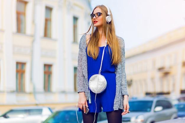 Retrato de moda ao ar livre de elegante mulher casual com fones de ouvido em macacão azul, bolsa prata posando contra ruas. apreciando uma música adorável. cores ensolaradas de verão.
