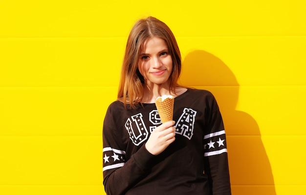 Retrato de moda ao ar livre de garota jovem hippie com sorvete na parede amarela