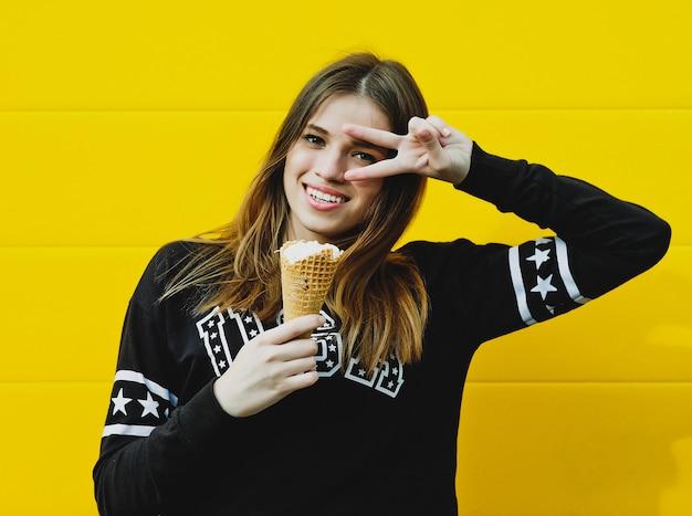 Retrato de moda ao ar livre de garota jovem hippie com sorvete no fundo da parede amarela