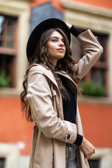 Retrato de moda ao ar livre de glamour sensual jovem elegante vestindo roupa de outono da moda e chapéu preto na rua