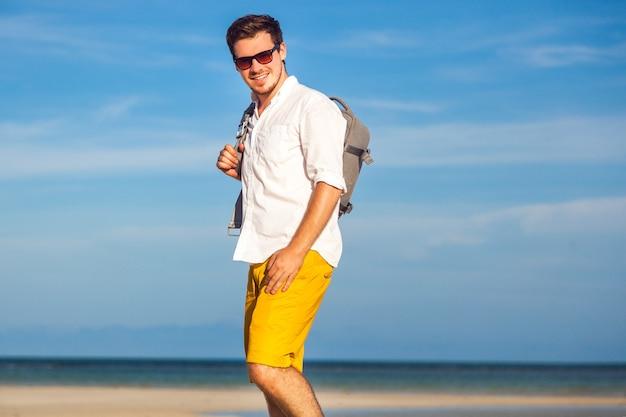 Retrato de moda ao ar livre de homem bonito posando na incrível praia tropical, em um belo dia de sol, bela vista do céu azul e do oceano, vestindo óculos escuros e camisa branca clássica de tipo amarelo casual.