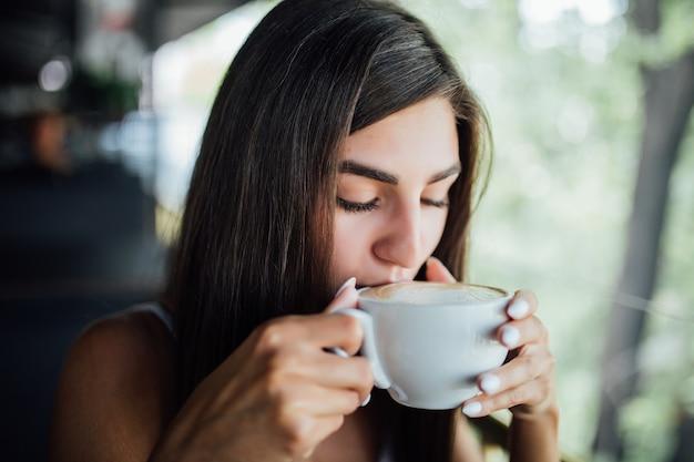 Retrato de moda ao ar livre de linda jovem bebendo chá e café