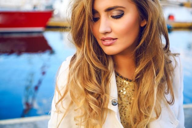 Retrato de moda ao ar livre de mulher bonita com uma pele perfeita, sonhando sozinha e olhando no chão. e curtir seus pensamentos, ter maquiagem natural, posando no porto marítimo.