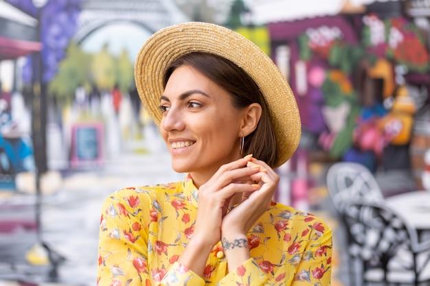 Retrato de moda ao ar livre de mulher com vestido amarelo de verão na parede colorida da rua