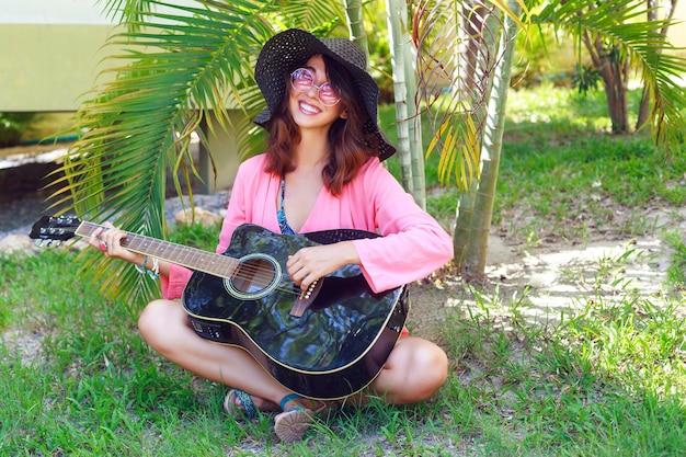 Retrato de moda ao ar livre de mulher hippie feliz muito sorridente, sentado na grama e segurando o violão. país tropical quente, fundo verde. roupa de verão com chapéu e óculos de sol rosa.