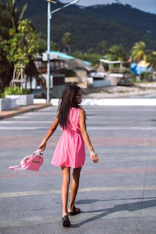 Retrato de moda ao ar livre de mulher tailandesa asiática muito magra posando na rua, usando um mini vestido rosa bonito, sandálias, óculos escuros e bolsa de correspondência de cores, humor de viagem.