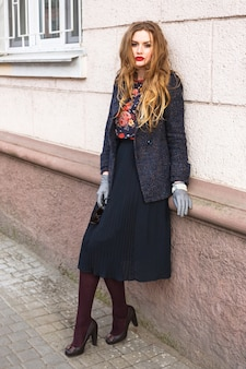 Retrato de moda ao ar livre de uma linda garota elegante posando na rua em um vestido de casaco elegante e elegante, com longos cabelos ruivos e acessórios que combinam perfeitamente.