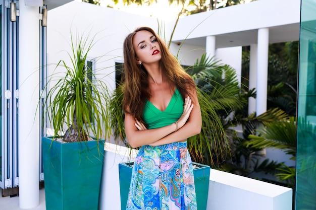 Retrato de moda ao ar livre de verão de uma mulher morena deslumbrante com cabelos longos e maquiagem brilhante, usando um vestido de seda sexy, posando em uma casa de luxo, luz do sol da noite