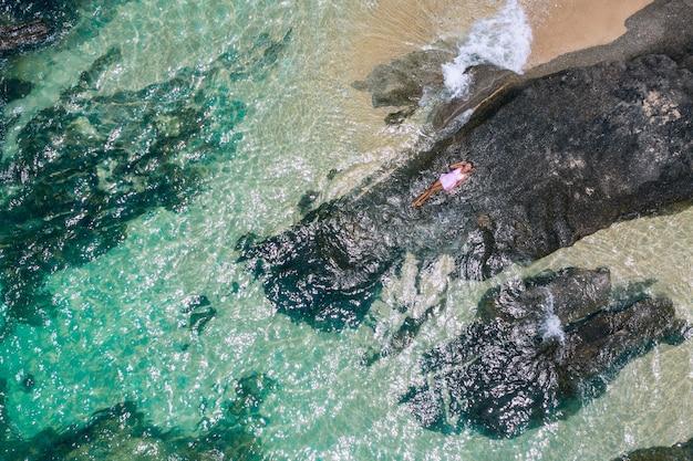 Retrato de moda ao ar livre estilo de vida de menina bonita, deitado sobre as grandes pedras no mar. usando vestido rosa curto elegante. solitário. foto art. criativo. vista do topo