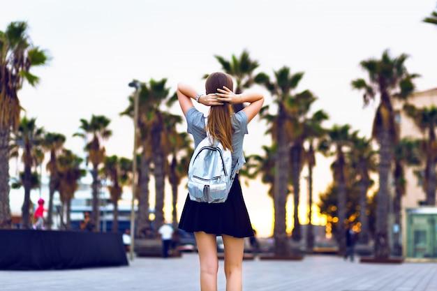 Retrato de moda ao ar livre, estilo de vida, de mulher jovem hippie caminhando em barcelona, viajar com mochila, roupa casual elegante, pôr do sol da noite, palmas das mãos, estudante, penteado loiro, tempo feliz, cores em tons.