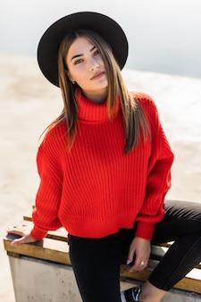 Retrato de moda ao ar livre, estilo de vida, de uma garota ruiva muito sorridente, sentada no banco