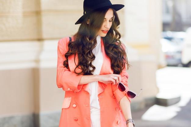 Retrato de moda ao ar livre perto de mulher casual elegante sexy de chapéu preto, terno rosa, blusa branca posando na rua velha. primavera, outono dia ensolarado. penteado ondulado.