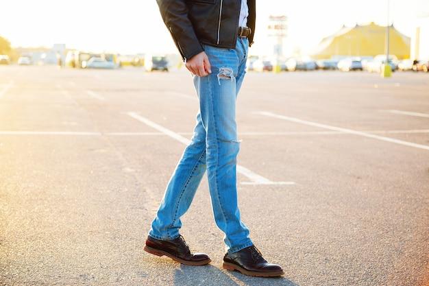 Retrato de moda ao ar livre urbano de homem jovem elegante hippie vestindo calças jeans de jaqueta de motociclista de couro e sapatos vintage posando no campo estacionamento noite luz solar.