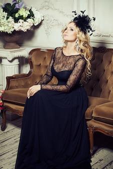 Retrato de moda arte de uma jovem mulher loira bonita elegante com brincos espumantes enormes, chapéu preto de moda com penas, maquiagem e penteado em um vestido de renda preta, posando em um sofá clássico marrom