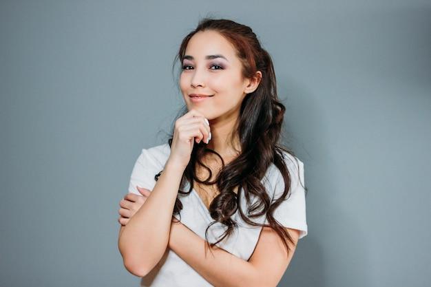 Retrato de moda beleza de sorridente sensual jovem mulher asiática com cabelo comprido escuro em t-shirt branca