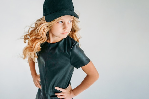 Retrato de moda beleza de sorrir garota de tween cabelo encaracolado em vestido de couro preto e boné de beisebol em branco isolado