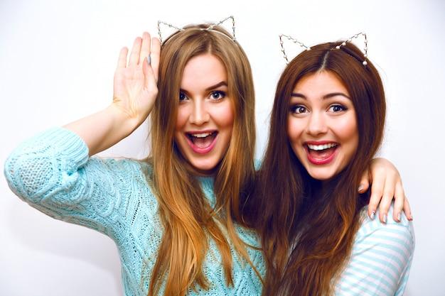 Retrato de moda bonito de mulheres bonitas irmãs se divertindo juntos, abraços e enlouquecendo, orelhas de gato engraçadas, suéteres de inverno hortelã, parede branca, melhores amigos, alegria, tendência, relações, maquiagem feliz, natural.
