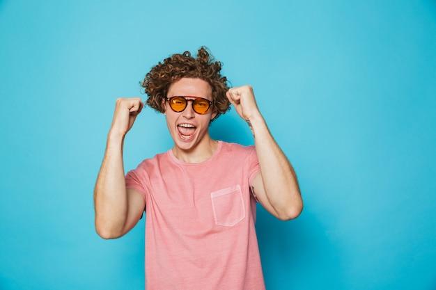 Retrato de moda cara com cabelo castanho encaracolado, usando óculos modernos, gritando e regozijando-se