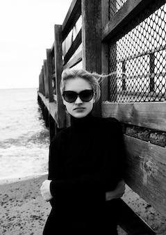 Retrato de moda clássica de mulher bonita à beira-mar ao lado da ponte