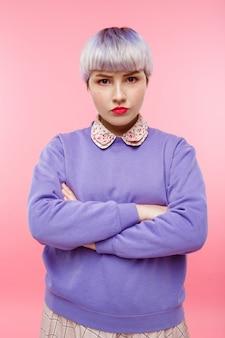 Retrato de moda close-up da menina bonitinha linda confiante com cabelo violeta leve curto, vestindo blusa lilás sobre parede rosa