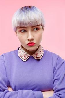 Retrato de moda close-up de brava linda garota dollish com cabelo violeta curto curto vestindo blusa lilás sobre parede rosa