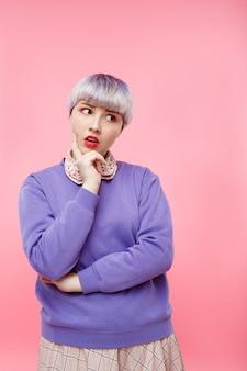 Retrato de moda close-up de querer saber linda garota dollish com cabelo violeta leve curto, vestindo blusa lilás sobre parede rosa
