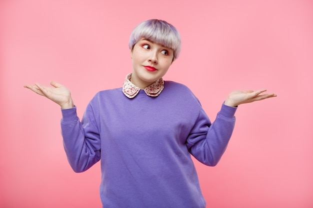 Retrato de moda close-up de surpresa linda garota dollish com cabelo violeta curto curto, vestindo blusa lilás sobre parede rosa