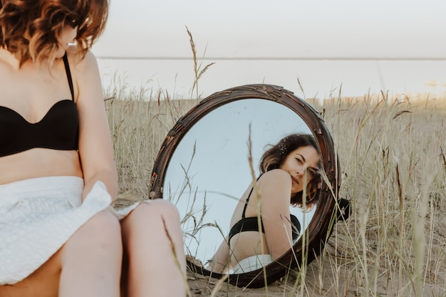 Retrato de moda estilo de vida da jovem mulher romântica d sentado na praia no reflexo do espelho