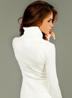Retrato de moda estilo de vida de uma jovem mulher bonita feliz em um vestido branco na parede cinza