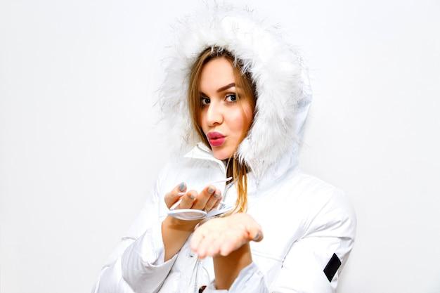 Retrato de moda estilo de vida interior de jovem loira vestindo parka branca de inverno, imagem com flash, cabelos longos, natural, maquiagem, alegria, diversão.