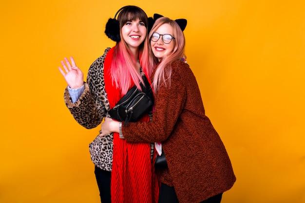 Retrato de moda estilo de vida primavera de duas mulheres felizes, sorrindo e se abraçando, melhores amigas posando, usando cachecóis de casacos da moda de pele e orelhas engraçadas.