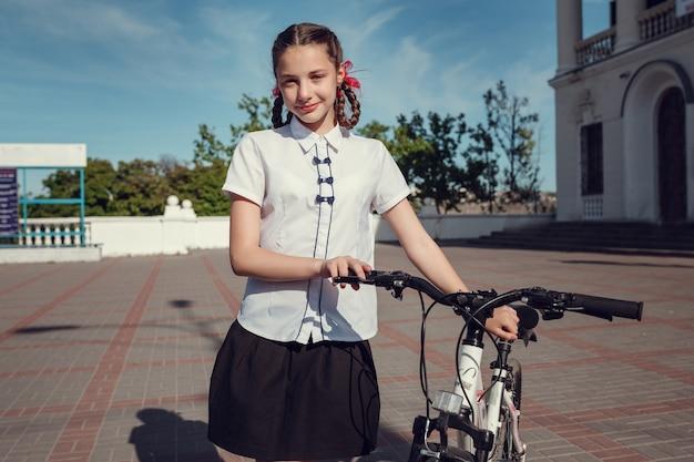 Retrato de moda feliz crianças se divertindo com a bicicleta na cidade.