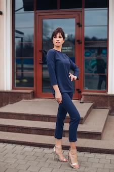 Retrato de moda feminina de corpo inteiro de uma bela morena em um terno azul esportivo com macacão e salto alto, posando na rua em frente ao edifício. estilo esporte chique. conceito de moda.
