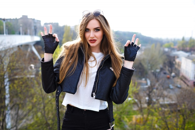 Retrato de moda grunge de mulher loira elegante, jaqueta de motoqueiro de couro e luvas, humor de rock n roll, vista urbana na ponte da cidade, moda de rua, penteado maquiagem, viajante.