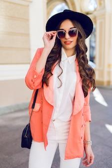 Retrato de moda hight ao ar livre de mulher casual elegante sexy chapéu preto, terno rosa, blusa branca posando na rua velha