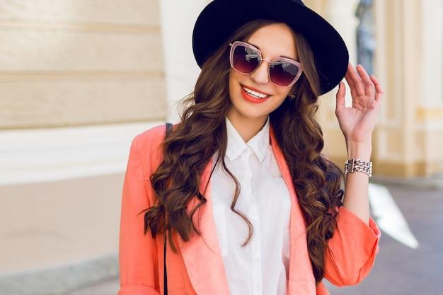 Retrato de moda hight ao ar livre de sexy elegante mulher casual de chapéu preto, terno rosa, blusa branca posando na rua velha. primavera, outono dia ensolarado. penteado ondulado.
