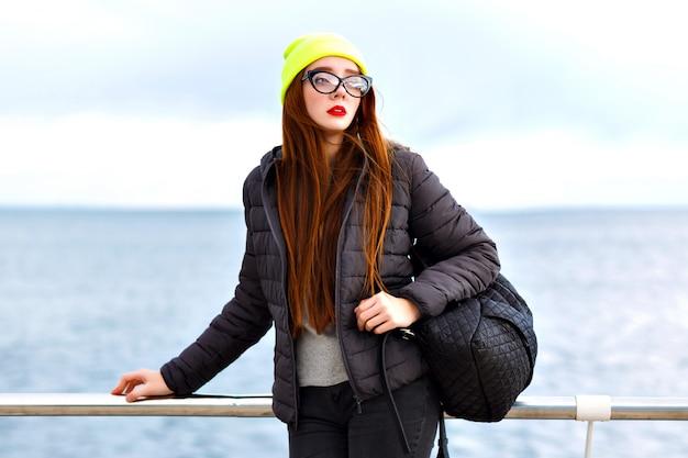 Retrato de moda hipster ao ar livre de uma jovem mulher bonita com longos cabelos ruivos, posando perto da beira-mar, viajando sozinho com a mochila, tempo frio, olhar de inverno elegante estilo de rua, chapéu, jaqueta, camisola.