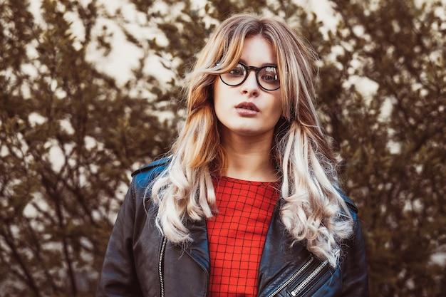 Retrato de moda hipster de jovem loira bonita posando ao ar livre no verão