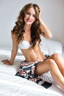 Retrato de moda interior de estilo de vida de mulher com incrível corpo sexy slim fit, posando na cama pela manhã, vestindo lingerie casual simples, relaxe e aproveite o dia ensolarado.