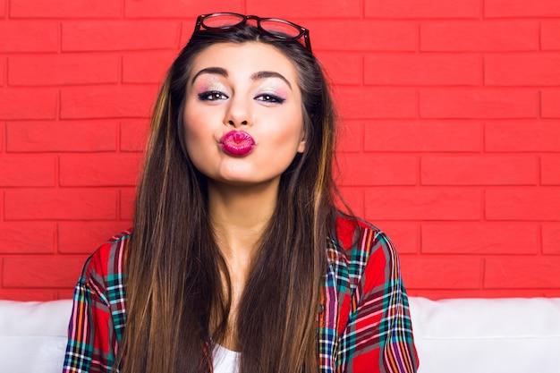 Retrato de moda interior de menina jovem adolescente bonita hippie se divertindo e enviando você e um beijo, vestindo roupa casual. brilhante.