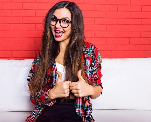 Retrato de moda interior de mulher jovem bonita hippie se divertindo e sorrindo, vestindo roupa casual. parede urbana vermelha brilhante.