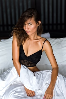 Retrato de moda interior de mulher morena sexy usando sutiã de renda preta e relaxar em seu estilo de vida luxuoso e ruim, beleza natural, tempo de manhã.