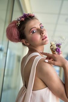 Retrato de moda jovem com flores no cabelo e maquiagem