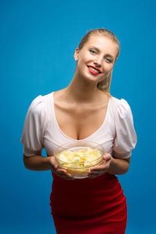 Retrato de moda jovem loira de vestido rosa-vermelho, maquiagem brilhante, segurando, comendo batata frita, batatas fritas e parede azul. alimentação não saudável. conceito de junk food
