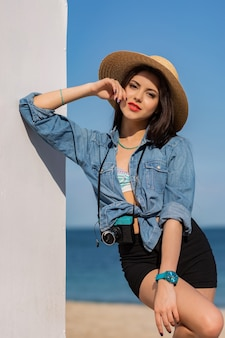 Retrato de moda verão ao ar livre de uma mulher linda com corpo bronzeado, lábios carnudos e vermelhos e pernas longas e fortes, posando na praia tropical ensolarada.