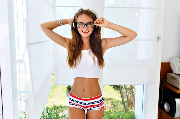 Retrato de moda verão de menina jovem hippie com corpo quente sexy perfeito ajuste, usando óculos vintage elegantes, mini shorts brilhantes e blusa cortada, ouvindo sua música favorita em fones de ouvido.