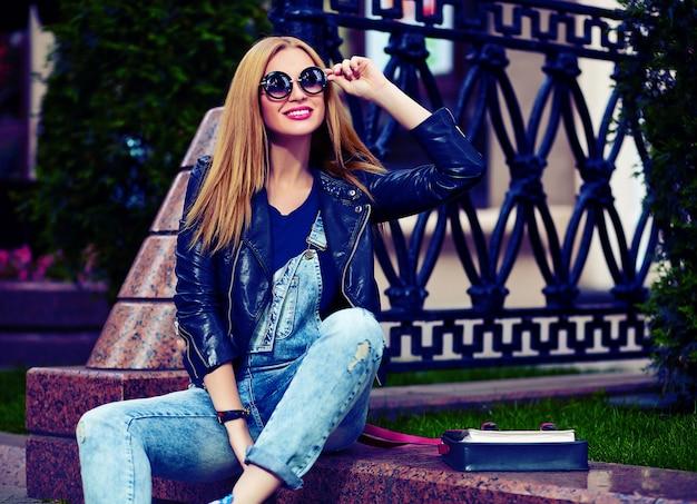 Retrato de modelo bonito engraçado moderno sexy urbano jovem mulher sorridente menina elegante pano moderno brilhante ao ar livre, sentado no parque em jeans em um banco em copos