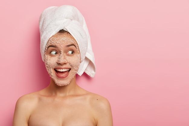 Retrato de modelo feminina feliz aplica esfoliante de sal marinho no rosto, tem expressão positiva, olha para o lado, está nu, usa toalha após o banho
