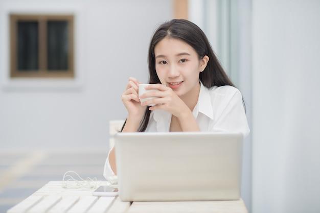Retrato de modelo feminino asiático bonito usa computador portátil para comunicação on-line; mulher de negócios feliz beber café sentado na mesa branca.